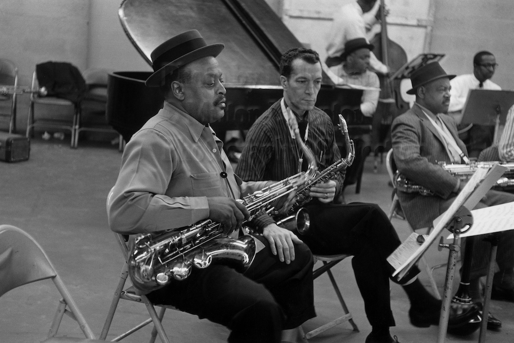 "Photo by Milt Hinton<br> © Milton J. Hinton<br>Photographic Collection <br><b class=""captionn"">In foreground:Ben Webster, Earle Warren, Coleman Hawkins; Count Basie (piano), Ed Jones (bass), and Freddie Greene (guitar), television studio (Sound of Jazz rehearsal), New York City, 1957</b>"