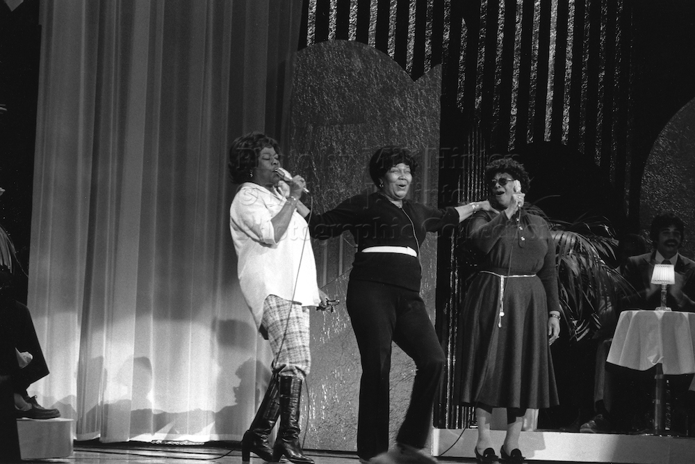 "Photo by Milt Hinton<br> © Milton J. Hinton<br> Photographic Collection <br> <b class=""captionn"">Sarah Vaughan, Pearl Bailey, and Ella Fitzgerald, rehearsal, television studio, Pasadena, 1979</b>"