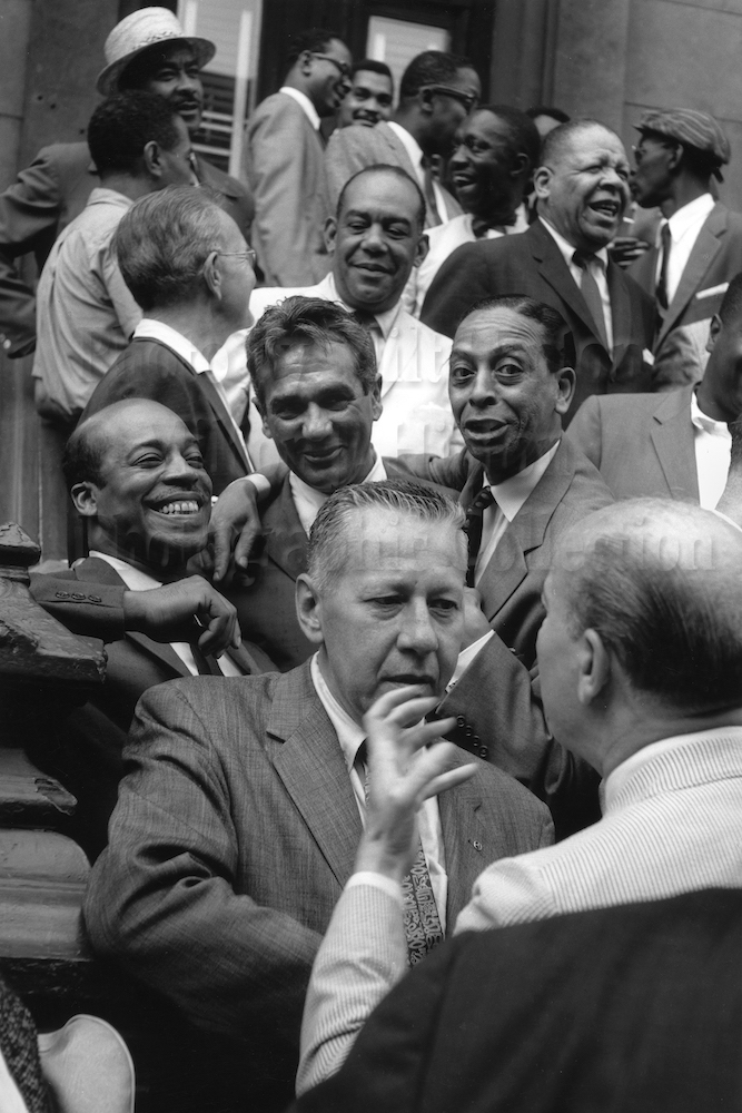 "Photo by Milt Hinton<br> © Milton J. Hinton<br> Photographic Collection <br> <b class=""captionn"">Front row: George Wettling and Bud Freeman; Second row: Jo Jones, Gene Krupa, Sonny Greer; Third row: Miff Mole, Zutty Singleton, and Red Allen; Fourth row: Dickie Wells, Art Blakey, and Taft Jordan; Top row: Buck Clayton, Benny Golson, Art Farmer, and Hilton Jefferson, Esquire magazine photo shoot, Harlem, New York City, 1958</b>"